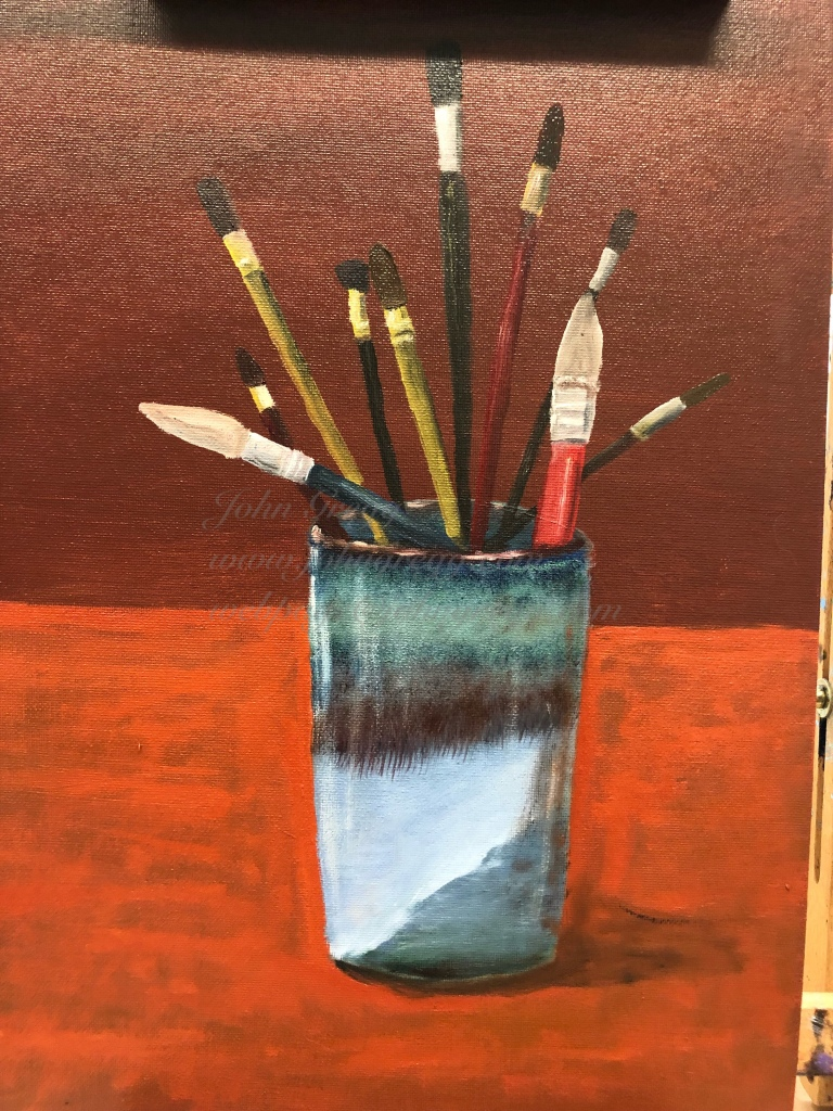 Paint brushes in blue cup